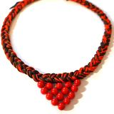 Red necklace braid from yarn with a decor stock image
