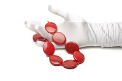 Red necklace female hand. Woman's hand in a white glove holding a red necklace Stock Images