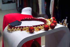Red necklace. Red gold necklace on a white table Royalty Free Stock Images