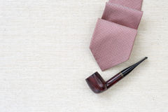 Red necktie and classic wooden pipe Royalty Free Stock Image