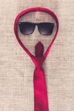 Red necktie and sunglasses on clean sackcloth Royalty Free Stock Photography