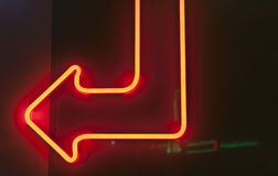 Red neon arrow on dark background. Stock Photography