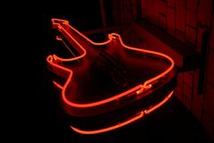 Red neon guitar. Neon guitar - symbol of rock cafe in Moscow Stock Image