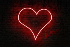 Red neon heart shaped sign on a brick wall royalty free stock image