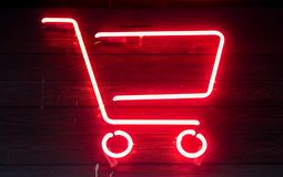 Red neon shopping cart on wooden surface royalty free stock photos