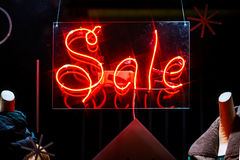 Red neon word Sale in shop window. At night stock photography