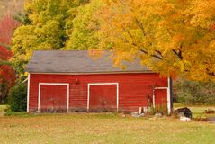 Red New England barn in autumn with colorful leaves stock photos