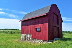 Red New England Barn in Hillsborough County, New Hampshire, United States US. Colorful rural red New England Barn surrounded by blue sky and green grass. Summer royalty free stock photography