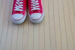 Red new sneakers on the wooden background Royalty Free Stock Photo