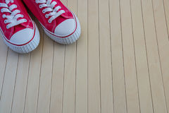 Red new sneakers on the wooden background Royalty Free Stock Images
