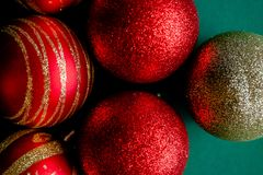 Red New Year Decorations Christmas balls. New Year Decorations Christmas balls, red and golden on green background royalty free stock photos