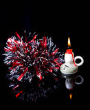 Red New Year's tinsel and the burning candle are reflected in bl Royalty Free Stock Photo