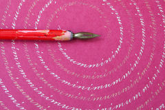 Red nib pen on pink paper textured background, abstract letters pattern. macro view, shallow depth of field Royalty Free Stock Photo