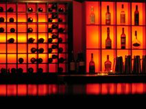 Red nightclub bar glowing bottles background. Ambient lighting reflecting of a bar with bottles of spirits and wine on shelves stock image