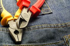 Red nippers yellow side cutter repair electrical engineering electricity close-up on jeans construction background base royalty free stock photography