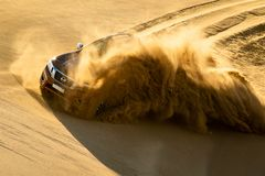 Red Nissan Vehicle Running on Sand Dune Stock Photography
