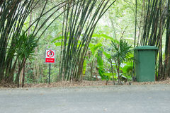 Red no littering sign. Green wood background Stock Photos