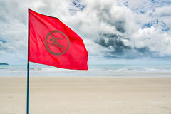 Red no swimming flag warning for tourist not to swim during stor Stock Photography