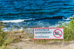Red no swimming sign posted on beach Royalty Free Stock Photography