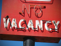 Red no vacancy sign. Neon red no vacancy motel sign with blue sky stock photo