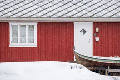 Red Norwegian residence with wooden boat on winter. Red Norwegian residence with wooden boat in blizzard on winter stock photos