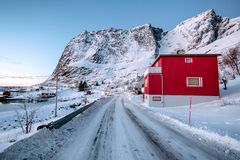 Red Norwegian village on beside highway. With snow in valley at coastline stock photo