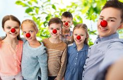 Happy childre taking selfie at red nose day. Red nose day, charity and childhood concept - happy children with clown noses taking selfie over green natural Royalty Free Stock Photos