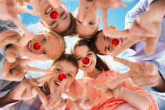 Children showing peace hand sign at red nose day stock photos