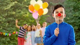 Happy boy with red clown nose at birthday party. Red nose day, party props and photo booth concept - smiling boy in blue hoodie with clown nose over group of stock photo