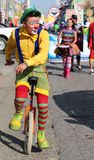 Red-nosed clown pedaling unicycle. Royalty Free Stock Photography