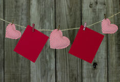 Red note cards and red and white striped hearts hanging on clothesline with antique wooden background Royalty Free Stock Images