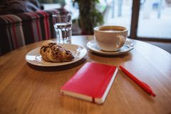 A red note and red pen is on the table in a cafe, a cup of coffee and a croissant on background stock images