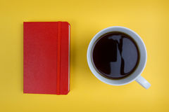 Red notebook and coffee cup on bright yellow background. Overhead shot of coffee cup and notebook royalty free stock images