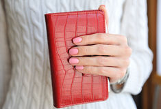 Red notebook in  female hand Royalty Free Stock Photography