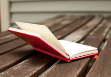 Red notebook open on wooden table Stock Image