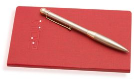 Red notebook and a pen Stock Image