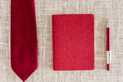 Red notebook, pen on clean sackcloth with red necktie Stock Images