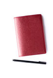 Red notebook with pen isolated Stock Photography