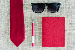 Red notebook, pen, sunglasses on clean sackcloth with red neckti Royalty Free Stock Images
