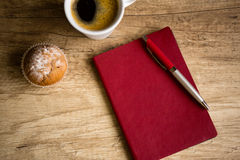 Red notebook with pen on wooden table Royalty Free Stock Photo