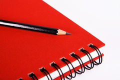 Red notebook with a pencil Stock Images