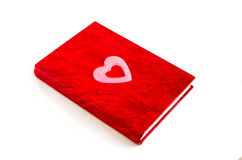Red notebook and pink heart. Red notebook on a white background Stock Image