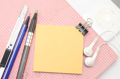Red notebook with post it and bulldog clip blue pen cutter ear p Stock Photo