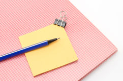 Red notebook with post it and bulldog clip blue pen isolated on Royalty Free Stock Photography