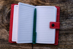 Red notebook on a wooden background Royalty Free Stock Photos