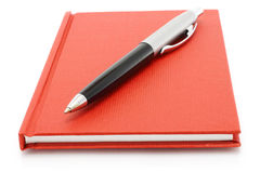 Red notepad with ball pen Stock Photos