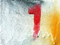 Red number one painting or spraying on the white, yellow, and black concrete wall with copy space. Spraying color, art and the winner concept Royalty Free Stock Images