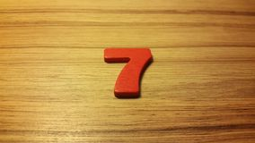 Red number 7 on wooden background Stock Photography