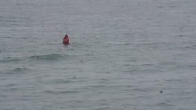 Red nun buoy 20 bobs in choppy waters