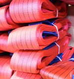 Red nylon soft lifting slings stacked in piles. Warehouse of finished products for industrial enterprises Stock Photo